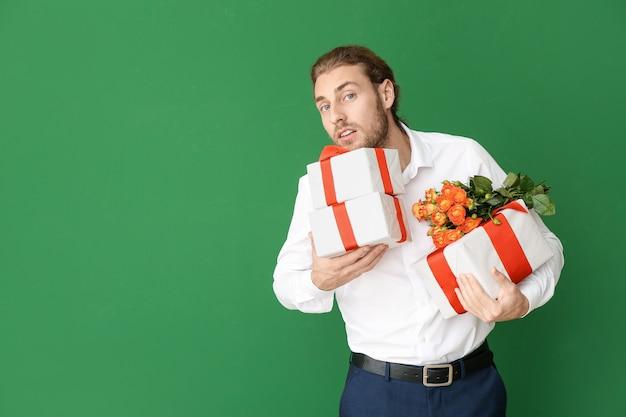 Knappe man met bloemen en geschenken op groen. valentijnsdag viering
