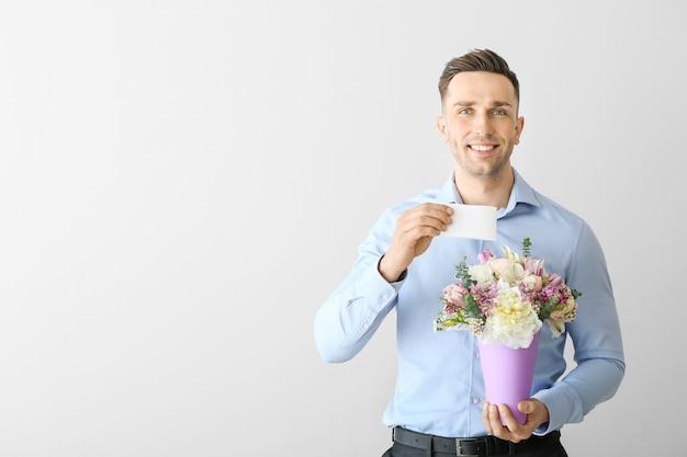 Knappe man met boeket van mooie bloemen en wenskaart