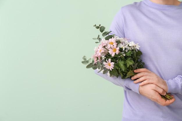 Knappe man met boeket van mooie bloemen op kleur