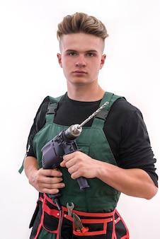 Knappe man met boormachine poseren geïsoleerd op wit. werknemer in overall