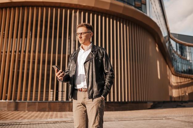 Knappe man met bril met een smartphone op straat van een grote stad. zakenman praten aan de telefoon op stedelijke achtergrond