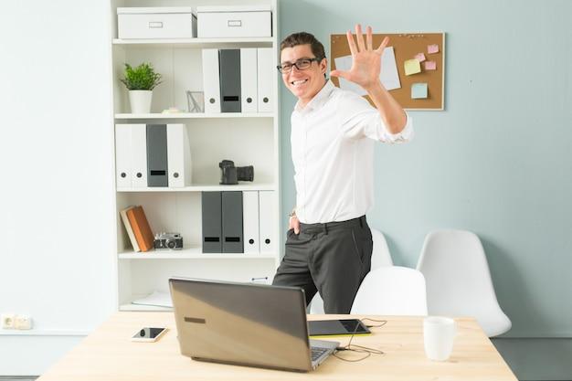 Knappe man met bril staat op kantoor in de buurt van een computer en een boekenplank