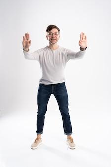 Knappe man met bril verbaasd en lacht naar de camera tijdens het presenteren met hand geïsoleerd op wit