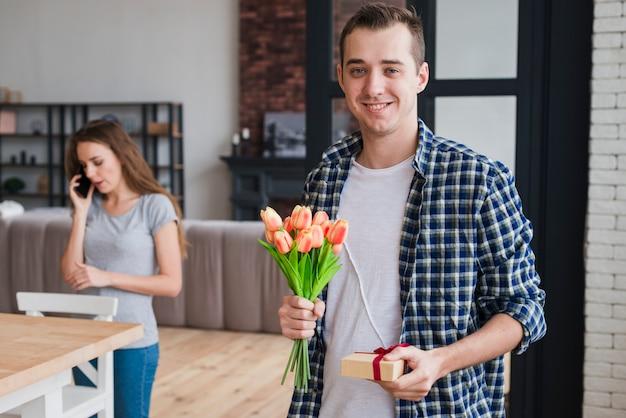 Knappe man met cadeautjes voor zijn vrouw