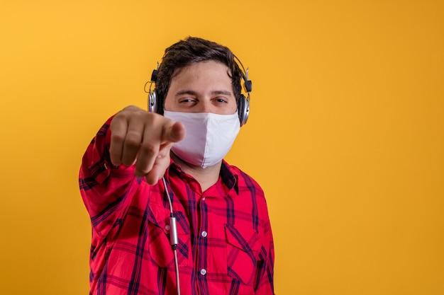 Knappe man met chirurgisch masker ter bescherming tegen covid en koptelefoon