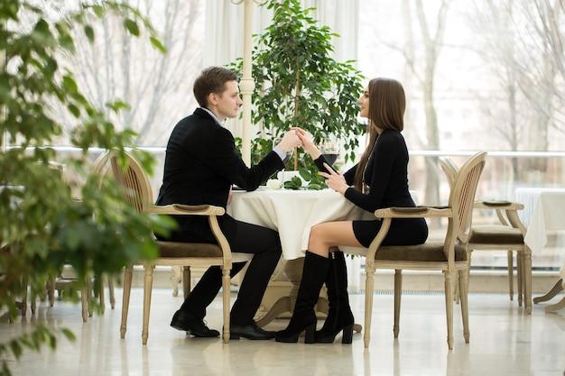 Knappe man met de hand van een meisje in een restaurant. valentijnsdag-concept