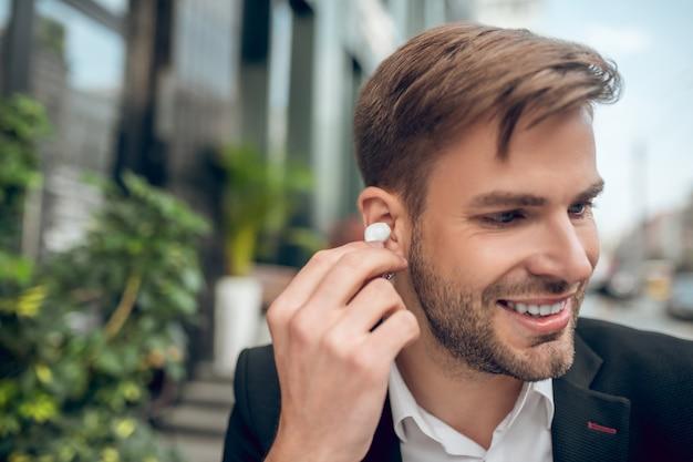 Knappe man met draadloze koptelefoon en glimlachen