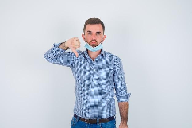 Knappe man met duim omlaag in shirt, spijkerbroek, masker en op zoek naar ontevreden, vooraanzicht.