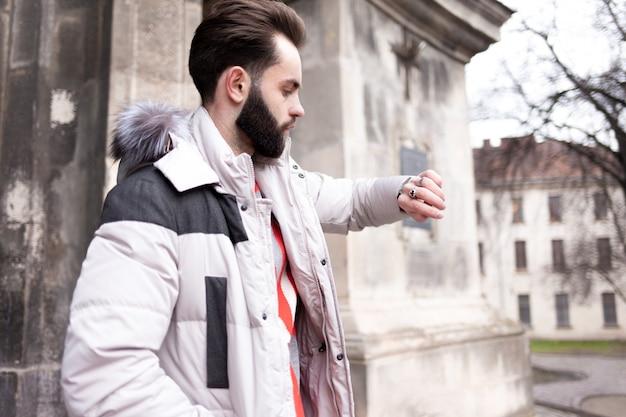 Knappe man met een baard kijkt op zijn horloge