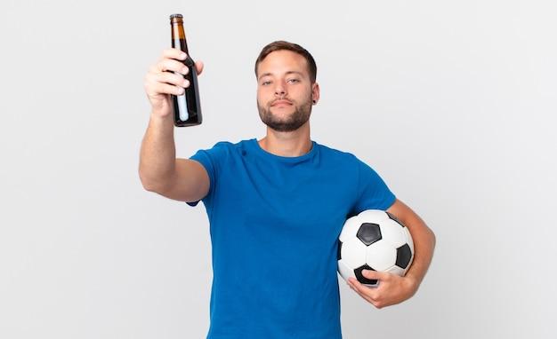 Knappe man met een biertje en een voetbal