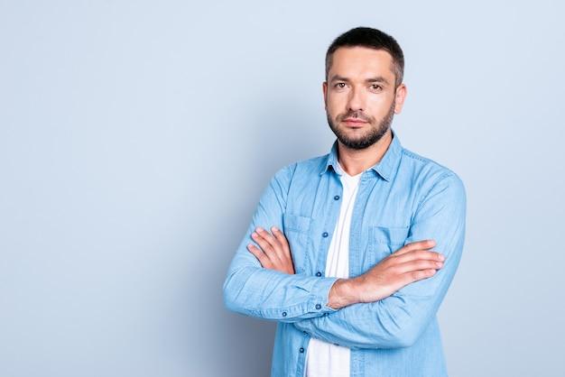 Knappe man met een blauw shirt poseren tegen de lichtblauwe muur