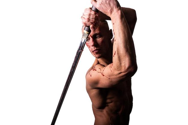 Knappe man met een blote torso en bloed. poseren met een zwaard. geïsoleerd op een witte achtergrond. voor welk doel dan ook.