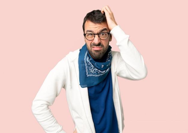 Knappe man met een bril met een uitdrukking van frustratie en niet begrijpen op geïsoleerde roze achtergrond