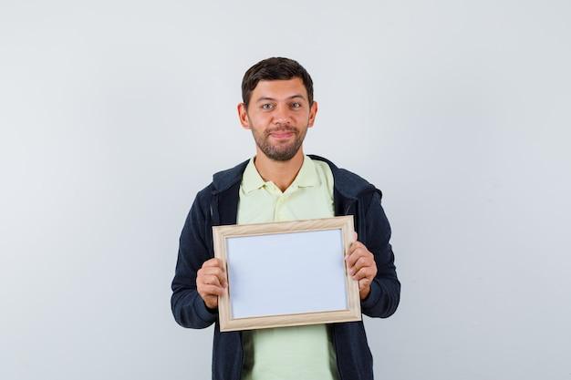 Knappe man met een fotolijst in een casual outfit