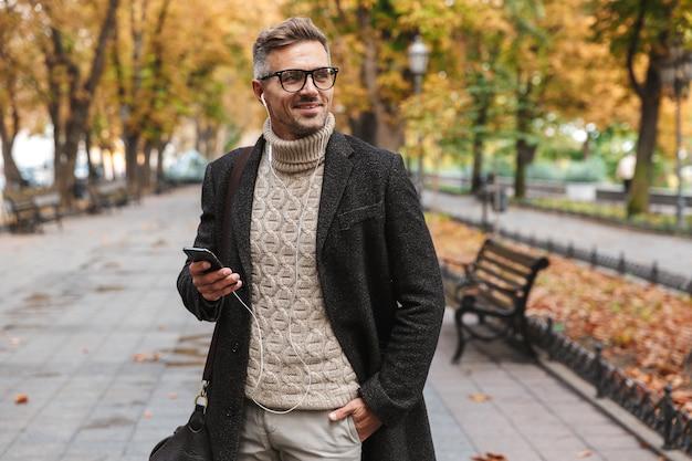 Knappe man met een jas buiten lopen, luisteren naar muziek met koptelefoon en mobiele telefoon