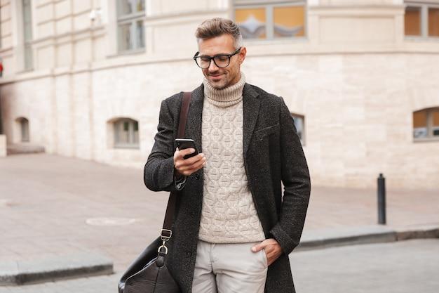 Knappe man met een jas buiten lopen, met mobiele telefoon