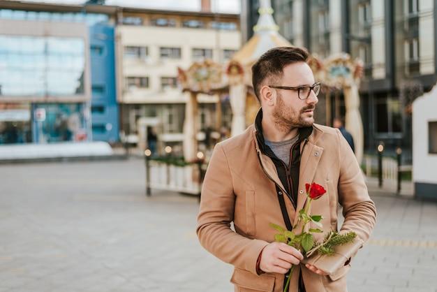 Knappe man met een roos die wacht op zijn date.