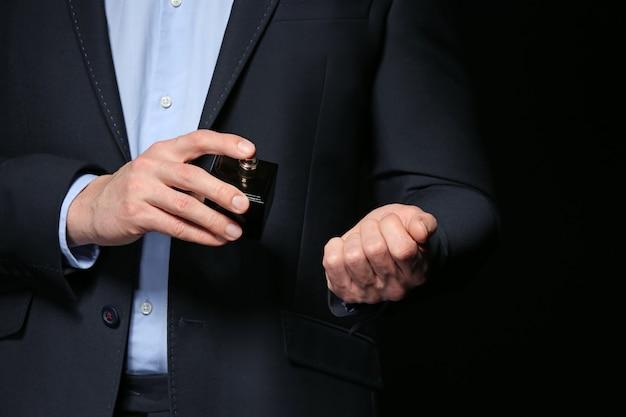 Knappe man met fles parfum op donkere achtergrond, close-up