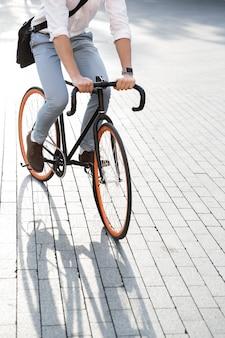 Knappe man met formele kleding, rijden op de fiets op straat in de stad