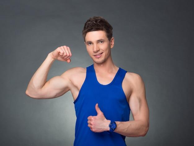 Knappe man met gekruiste armen op zoek naar links op zwarte achtergrond, blauw t-shirt