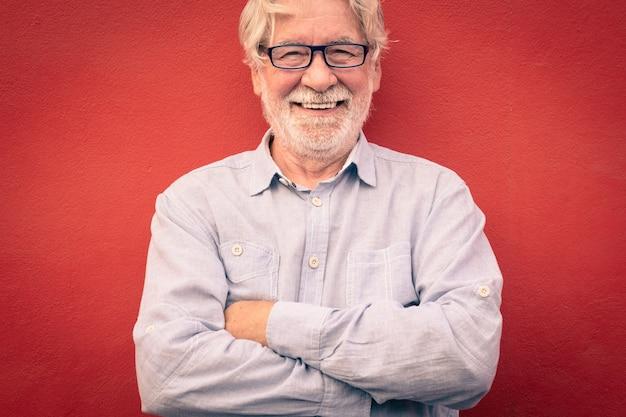 Knappe man met gekruiste armen staande op rode achtergrond, glimlachend gelukkig kijkend naar de camera, blanke senior mensen met witte baard en haar