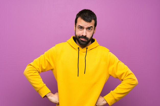Knappe man met gele boos sweatshirt