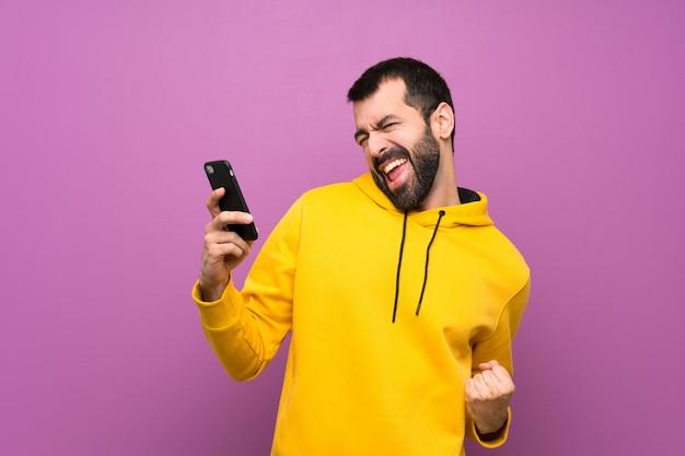 Knappe man met gele sweater met telefoon in overwinning positie