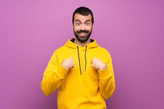 Knappe man met gele sweater met verrassing gezichtsuitdrukking
