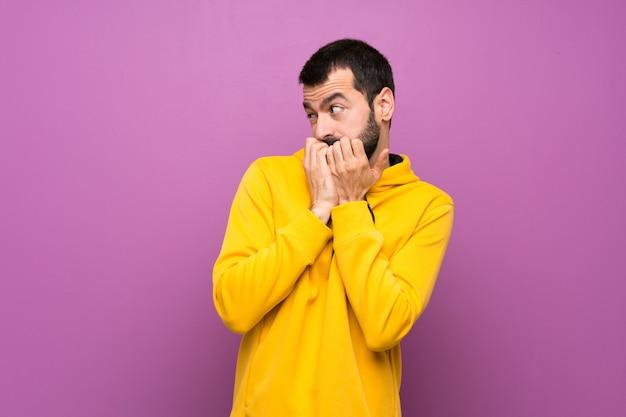 Knappe man met gele sweater nerveus en bang om handen naar mond te brengen