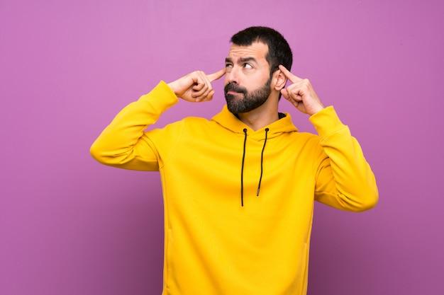 Knappe man met gele sweater twijfels en denken