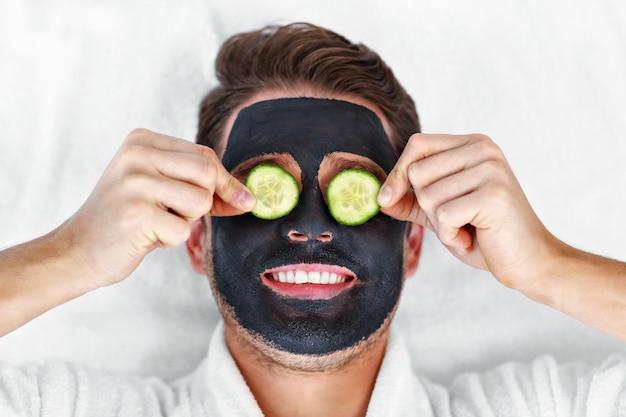 Knappe man met gezichtsbehandeling in spa salon
