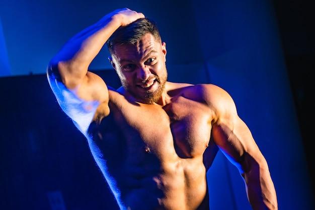 Knappe man met grote spieren, poseren in de sportschool