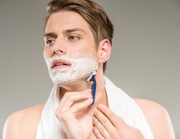 Knappe man met handdoek op schouders scheren na bad.