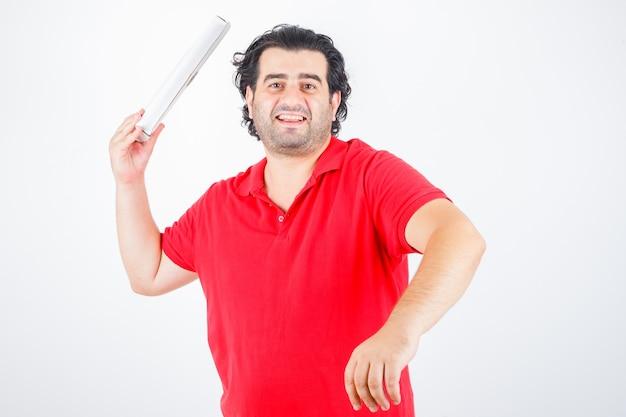 Knappe man met kartonnen doos, glimlachend in rood t-shirt en op zoek vrolijk. vooraanzicht.