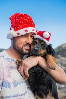 Knappe man met kerstmuts en in zijn armen zijn hond gekleed voor kerstmis.