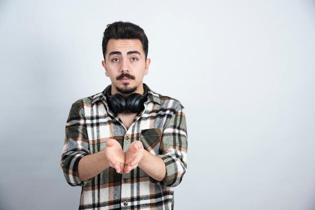 Knappe man met koptelefoon staande over witte muur.