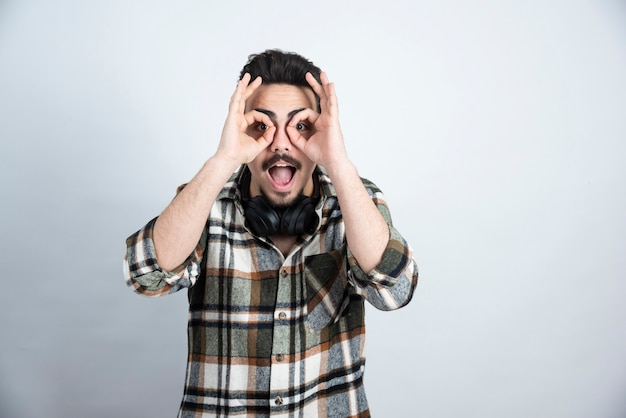 Knappe man met koptelefoon verrekijker ogen maken over witte muur.