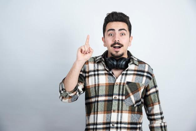 Knappe man met koptelefoon wijzend op witte muur.