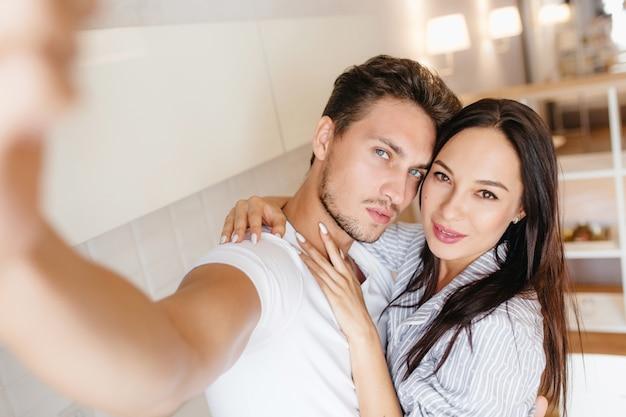 Knappe man met kort haar die een foto van zichzelf neemt terwijl zijn vrouw hem omhelst