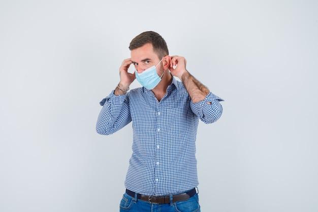 Knappe man met masker in shirt, spijkerbroek en op zoek naar serieuze, vooraanzicht.