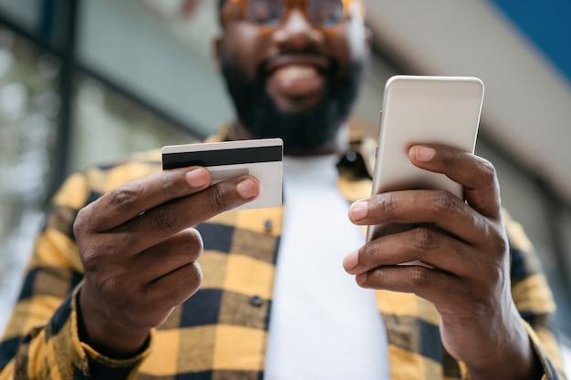 Knappe man met mobiel en online winkelen