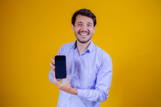 Knappe man met mobiele telefoon in handen wijzend met ruimte voor tekst