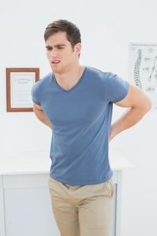 Knappe man met pijn in de rug in het kantoor