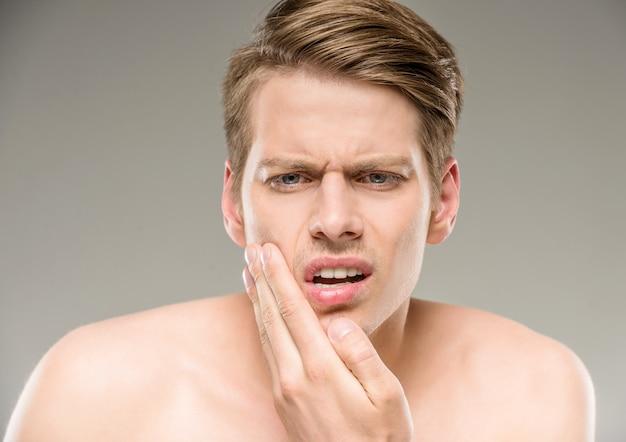 Knappe man met pure huid aan zijn gezicht te raken.