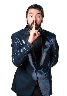 Knappe man met sequin jas die stilte gebaar maakt