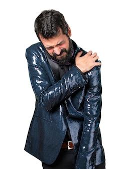 Knappe man met sequin jas met schouderpijn