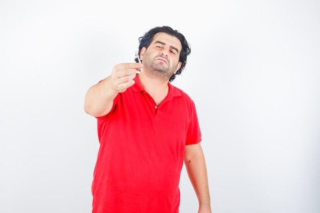 Knappe man met sigaret in rood t-shirt en op zoek naar serieus. vooraanzicht.