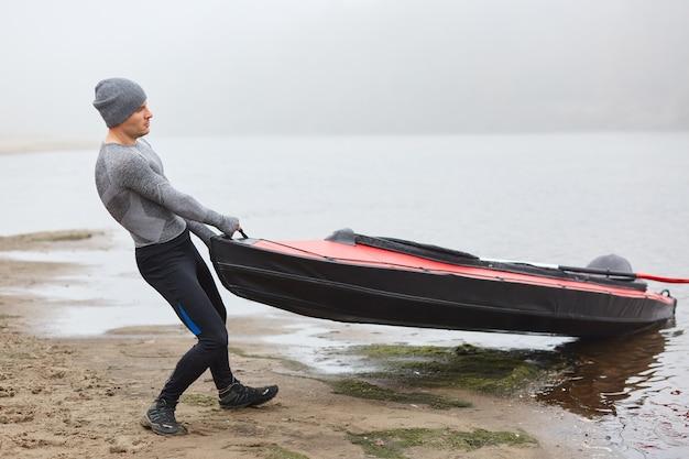 Knappe man met sportieve slijtage en pet die kajak naar de oever trekt uit het water