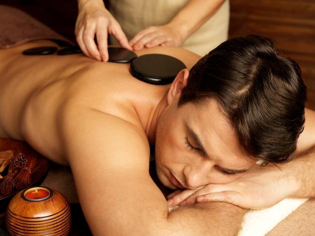 Knappe man met stenen massage in spa salon. gezonde levensstijl.