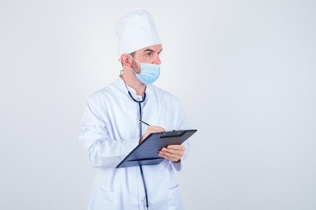 Knappe man met stethoscoop om nek, notities schrijven op klembord in witte medische laboratoriumjas, masker en peinzend, vooraanzicht kijken.